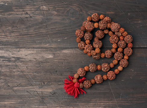 Rudraksha prayer beads for meditation on a brown wooden background, top view