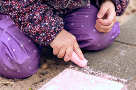 Midsection Of Child Drawing With Chalk On Floor