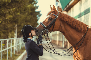 Young teenage girl equestrian kissing her favorite red horse. Multicolored outdoors horizontal image. Dressage outfit  Papier Peint