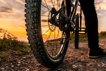 Mountain bike rear wheel detail. Back shot of mountain bike on sunset. Mountain bike tire.