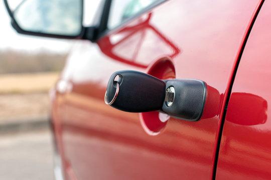 new black car key sticks out in a car door closeup