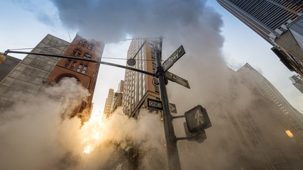 Low Angle View Of Street Light Amidst Smoke Against Skyscrapers In City