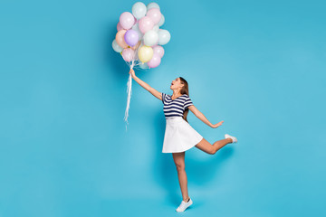 Full size profile photo of beautiful funky lady hold many colorful balloons fly up wind blowing wear striped t-shirt white short skirt footwear isolated blue color background