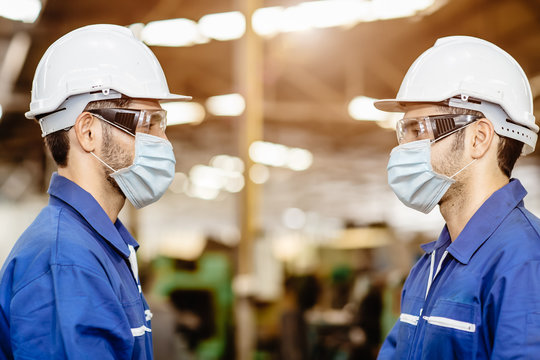 Worker wear face mask standing distancing during talking together service woking in factory to prevent Covid-19 virus air dust pollution and for good healthy.