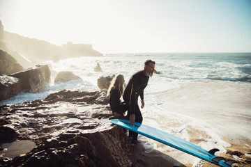 Senior couple sitting together on rocks with surfboards taking a break