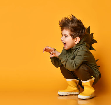 Brunet kid boy model in brown dino hoodie sits squatting, growling and scaring you, holding hands like a beast claws