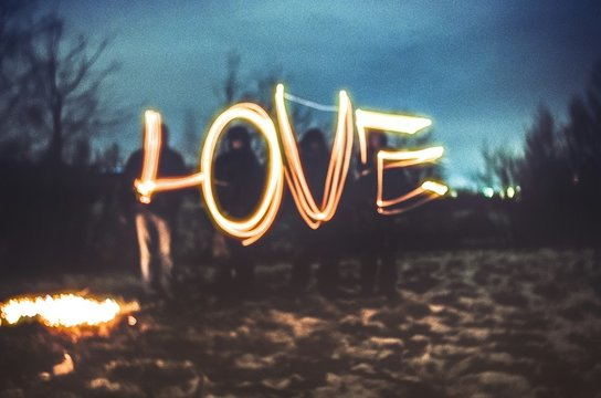 Friends Standing With Illuminated Love Light Painting By Campfire Against Sky At Night