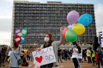 Israeli kindergarten's teachers and others wear face masks as they protest against the government plan to reopen kindergartens and schools for young children amid the coronavirus disease (COVID-19) outbreak  at Rabin square, Tel Aviv