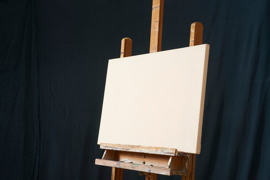 traditional oil Primed Linen stretched canvas panel painting support. Fresh GESSO priming. On an easel . Dark background isolated cool artist studio mockup