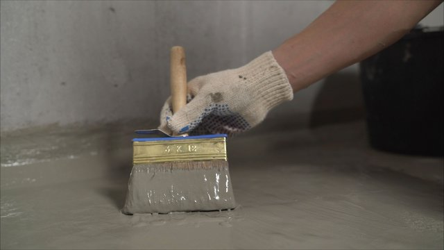 Waterproofing concrete floor with mortar and brush. An industrial worker at a construction site installs a sealant for waterproofing cement.