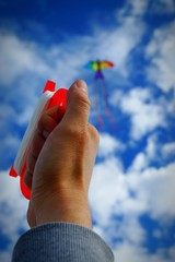 Cropped Image Of Hand Flying Kite Against Sky