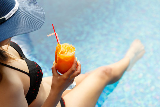 Woman in a blue summer hat relaxing at the pool with a cocktail