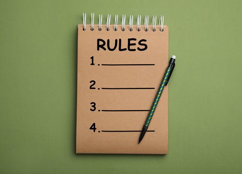 Kraft notebook with list of rules and pencil on green background, top view