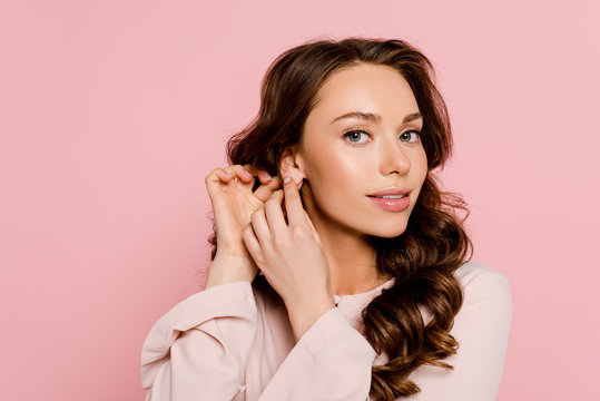 attractive young woman touching ear isolated on pink