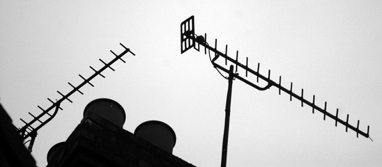 Low Angle View Of Silhouette Smoke Stacks And Television Aerial