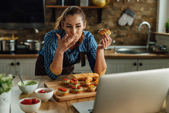 Young woman using laptop while eating bruschetta in the kitchen.