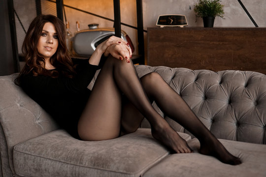 Sexy beautiful woman with long hair and a black transparent pantyhose lying on a sofa