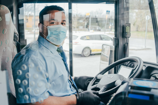 bus driver with mask wearing protecting gloves on his hand in bus to protect himself
