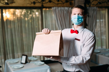 Food delivery from the restaurant. Portrait of a waiter holding a craft paper bag for food delivery.