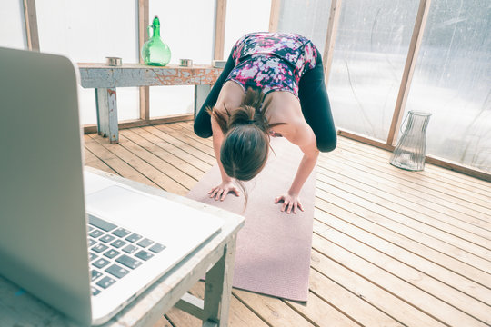 Young woman is doing crane pose for balance. Yoga practice at home studio due to COVID-19. She follows online yoga course on the computer. Healthy lifestyle photo and urban interior.