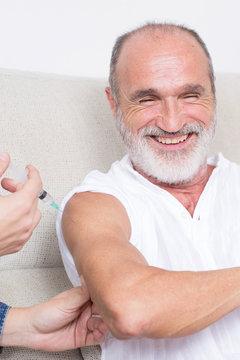 Happy elderly senior gets a vaccine in times of coronavirus
