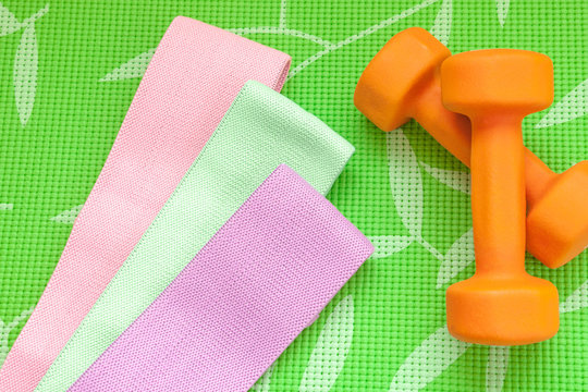 Orange dumbbell for fitness and sports elastic bands on a green background, concept of home workouts