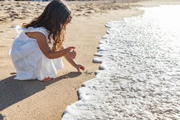 Niña jugando en la playa vestida de blanco con una estrella de mar  Fotobehang