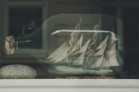 Close-up Of Miniature Ship On Bottle Seen Through Glass
