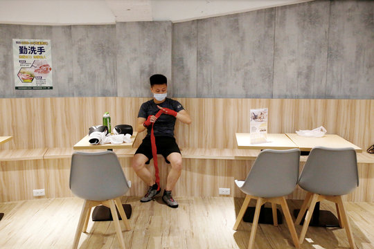 A student of a martial arts center prepares for class while wearing a surgical mask to protect himself from the coronavirus disease (COVID-19) in Taipei