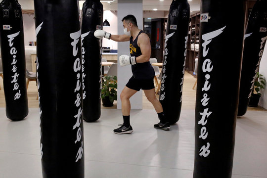 A student of a martial arts center trains while wearing a surgical mask to protect himself from the coronavirus disease (COVID-19) in Taipei