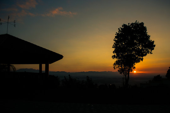 Weather Vane On Roofed Structure By Silhouetted Mountains And Trees At Dusk