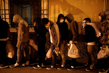 Guatemalan migrants queue to enter a hotel after being deported from the U.S., in Guatemala City