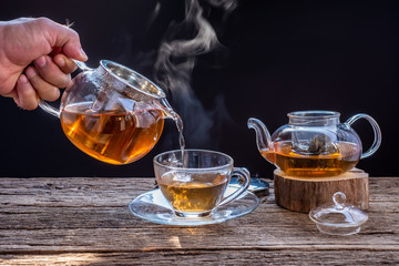 A cup of tea on a wooden table,process brewing tea,Cup of freshly brewed fruit and herbal tea, darker background. .Hot water is poured from the kettle into a cup with tea.