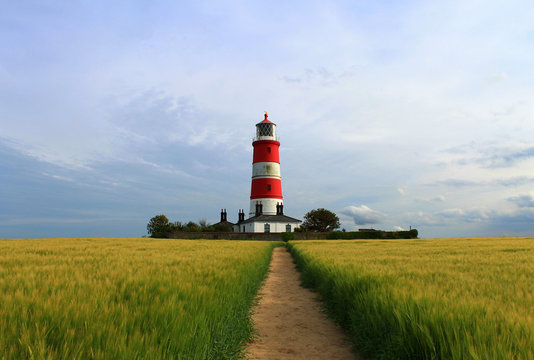 Trail On Grassy Field Leading Towards Happisburgh Lighthouse Against Cloudy Sky