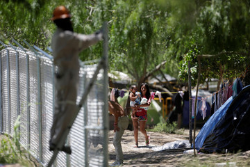 A migrant woman carries a baby near to an employee working on a fence placed around a migrant encampment, where more than 2,000 people live while seeking asylum in the U.S, as the spread of the coronavirus disease (COVID-19) continues, in Matamoros