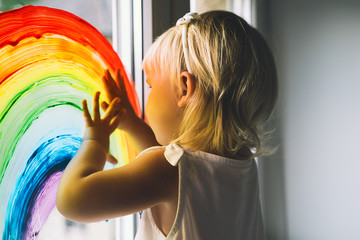 Little girl hands touch painting rainbow on window.