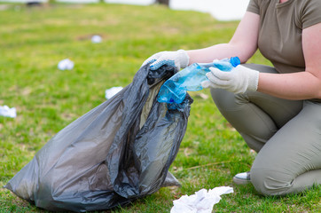 A volunteer cleans the park of scattered debris, collecting it in a bag. The hands of an environmentalist put plastic trash in a black bag. Ecology, environmental protection concept.