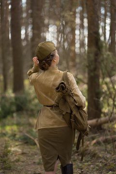 girl in uniform in the forest with a backpack
