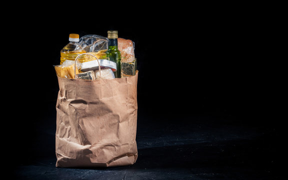 Paper bag with products on a dark background. Food donations