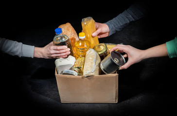 Volunteers putting different products in donation boxes on dark background