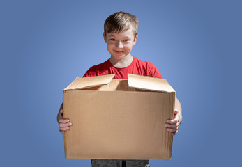 Boy holding a cardboard box on dark background. Donatation. Copy space for text