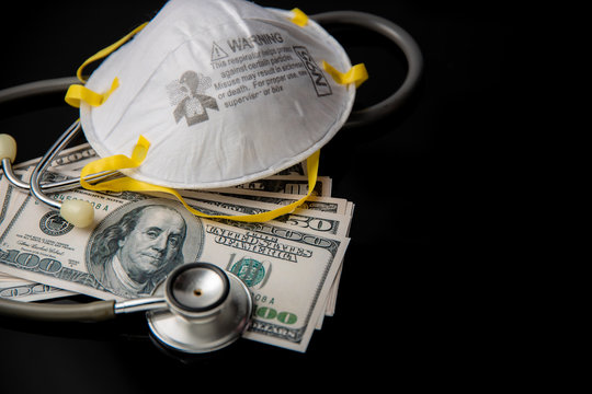 Concept of economy crisis and recession in USA during coronavirus or covid-19 pandemic with N95 mask US dollars stethoscope and black background copy space