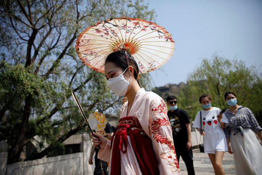 A woman wearing face mask and traditional Chinese clothing visits Gubei Water Town on the first day of the five-day Labour Day holiday, following the coronavirus disease (COVID-19) outbreak, on the outskirts of Beijing