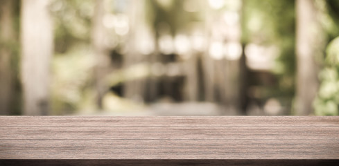Empty wooden table top and green nature bokeh for display product