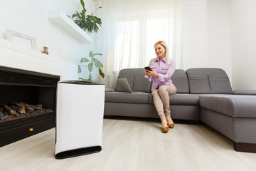 Young woman relaxing on the couch while air humidifier or purifier working on the foreground. Controlling it with a smartphone remotely