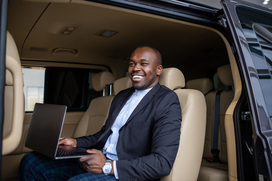 African successful businessman working at a laptop with a grin sitting in the beige interior of a large car