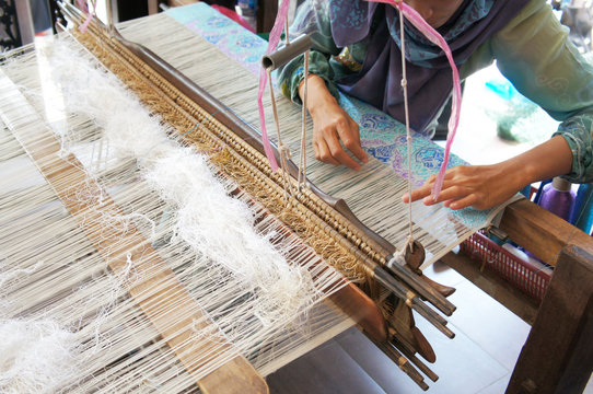 A woman is using traditional weaving machines to weave songket. Songket is a Malay traditional clothes with high quality and value.