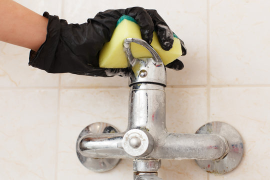 Limescale crust on bathroom mixer faucet. Hands in disposable rubber (latex or vinyl) gloves cleaning hard water calcium carbonate deposit on sink or bath tap. Dirty plumbing covered with lime scale