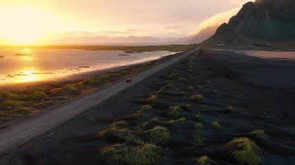 Wall Mural - Car drives on a dirt road at sunset with Vestrahorn mountain in Iceland