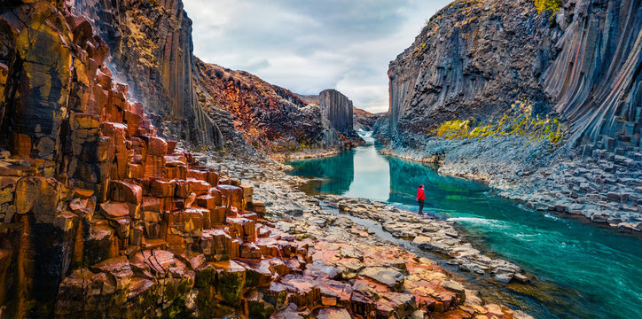 Tourist went to the bottom of canyon and admired the beauty of basalt columns. View from flying drone of Studlagil Canyon. Picturesque summer scene of Iceland, Europe.